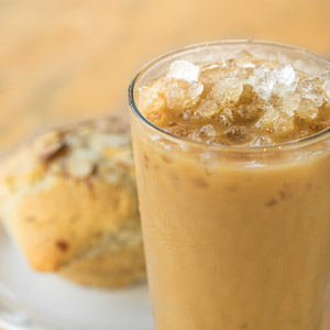 iced coffee in a pint glass, sitting beside a muffin