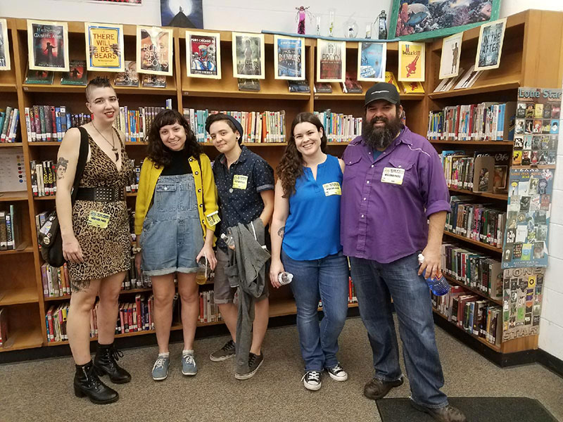 bennu staff standing in front of a row of bookcases at Webb Middle School